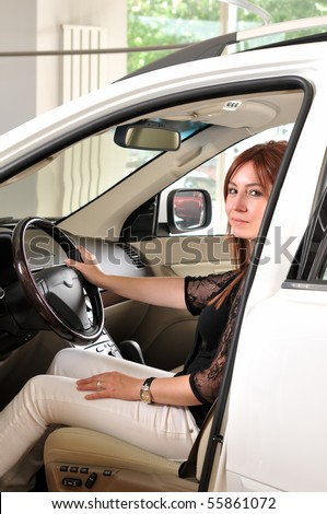 Female driver testing a new car at a showroom of dealer - a series of BUYING A NEW CAR images. - stock photo