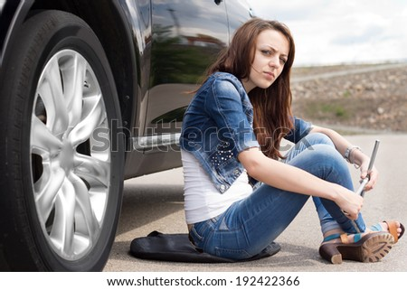 Female driver waiting for roadside assistance sitting on the road alongside her car with the wheel spanner in her hand with a bored expression - stock photo
