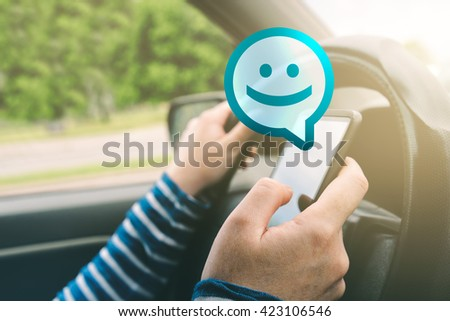 Female driving car and receiving smiley emoticon message on smartphone, using mobile device in traffic, selective focus - stock photo