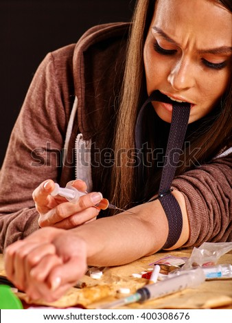 Female drug addict with  tourniquet on his arm and  syringe. Girl tightens a tourniquet teeth. - stock photo