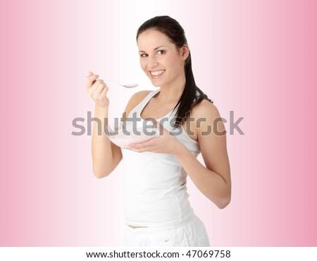 Female eating yogurt over pink background - stock photo