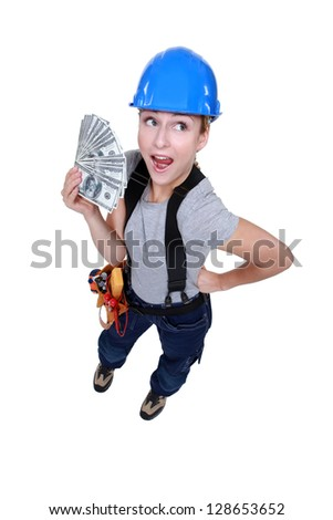 female electrician holding bunch of dollars - stock photo