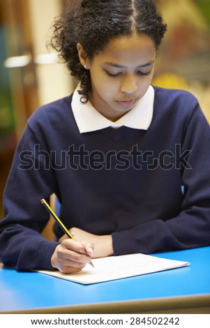 Female Elementary School Pupil Writing Book In Classroom - stock photo