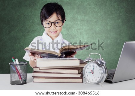 Female elementary school student back to school and reading books in the class with laptop, alarm clock, and stationery on the table - stock photo