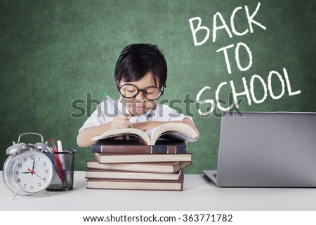 Female elementary school student back to school and writing on the book in the class - stock photo