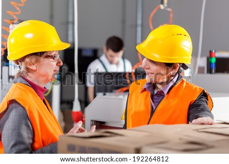 Female employees discussing at production area, horizontal