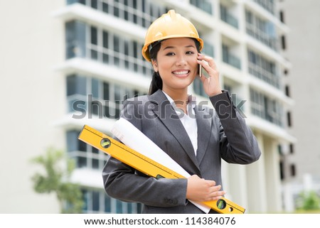Female engineer consulting by phone right from the construction site
