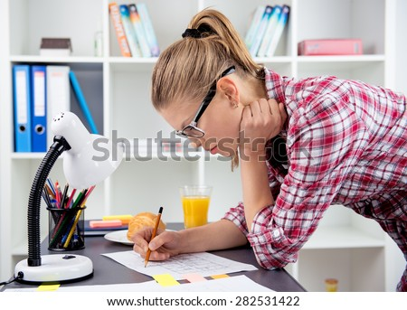 Female engineer drawing sketch of building working at home. Young architect constructor studying blueprint at the desk.  - stock photo