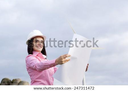 Female engineer holding a blueprint at wind turbine site - stock photo