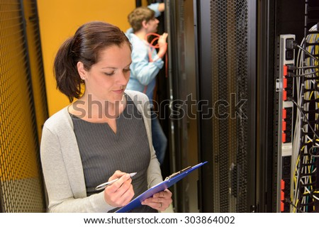 Female engineer in datacenter by network servers - stock photo