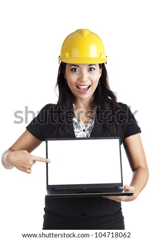 Female engineer pointing at a copy space on the blank screen of ultrabook laptop computer - stock photo