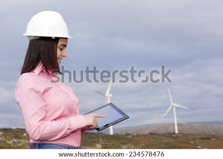 Female engineer using a tablet at wind turbine site