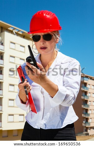 Female engineer with red helmet using a mobile phone at construction site. - stock photo
