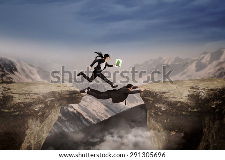 Female entrepreneur get a help from her partner for through a cliff on mountain - stock photo