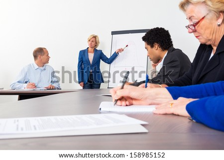 Female entrepreneur giving presentation on filpchart to colleagues in conference room - stock photo