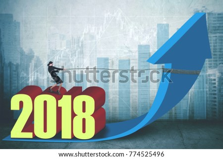 Female entrepreneur pulling an upward arrow while standing above number 2018 with growth graph and modern city background