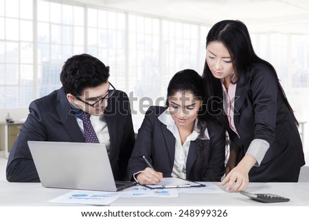 Female entrepreneur signing a business contract with two partners looking her