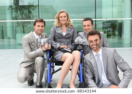 Female executive in wheelchair with colleagues outside office building - stock photo