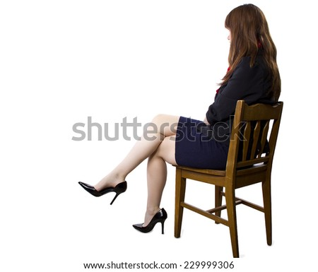 female executive sitting on a chair showing legs and heels on white background - stock photo