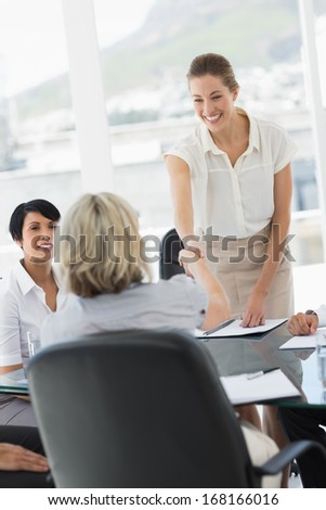 Female executives shaking hands during a business meeting in the office - stock photo