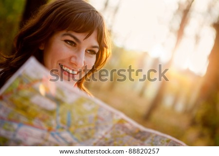 female explorer looking at a map outdoors - stock photo