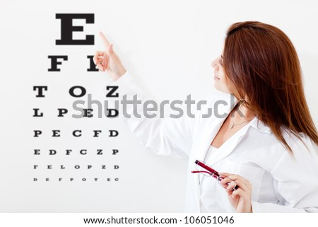 Female eye doctor making a vision test with letters on a board - stock photo