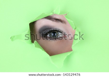 Female eye looking through hole in sheet of paper - stock photo