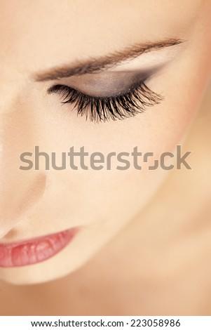 female eyebrow and eye with false eyelashes - stock photo