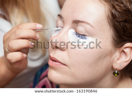 Female eyelashes dyeing with permanent blue makeup