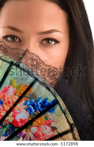 female eyes behind fan - stock photo