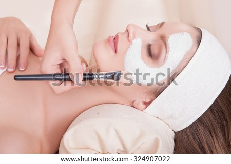 Female face closeup girl mask is applied with a brush. Beautiful girl in a beauty salon on the procedures for rejuvenation, skin lifting. Lovely woman with soft skin lying on his back in the salon spa - stock photo