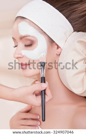 Female face with a white mask.Cute woman with perfect skin in beauty salon on the procedures for the care of skin.Cosmetology.BEAUTY SALON.Girl with dark hair lying on her back in the beauty salon - stock photo