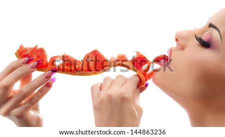 Female face with pummelo slice over white background - stock photo