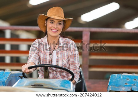female farmer driving a tractor in farm house - stock photo