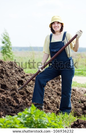 Female farmer works with manure at field