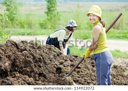 Female farmers works with manure at farm