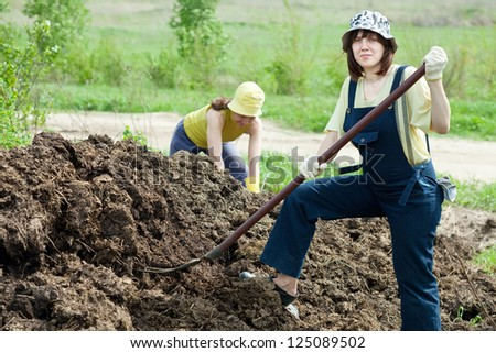 Female farmers works with manure at farm - stock photo