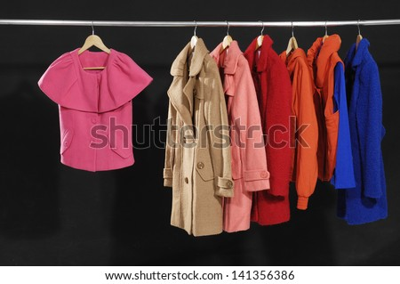 female fashion clothing with set of coat on hangers at the show