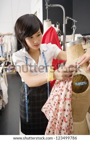 Female fashion designer pinning costume on mannequin - stock photo