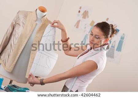 Female fashion designer working with pattern cutting at studio - stock photo