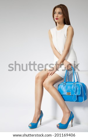 female fashion model sitting on the wooden block. - stock photo