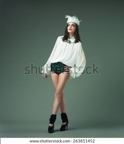 female fashion model wearing sexy clothing and feather headband, against grey background - stock photo