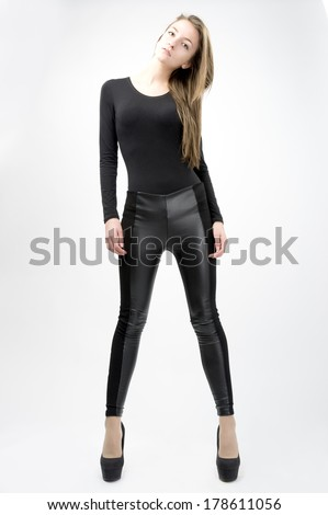 female fashion model wearing tight black pants black top long sleeves black shoes high heels  - stock photo