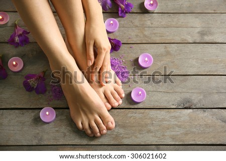 Female feet at spa pedicure procedure with flowers and candlelight on wooden background - stock photo