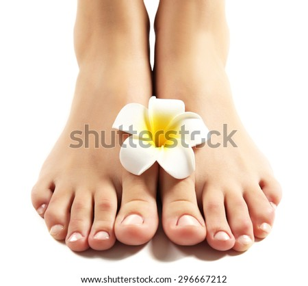 Female feet at spa pedicure procedure with plumeria isolated on white - stock photo