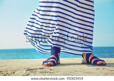 female feet in billowing dress against the background of the ocean - stock photo