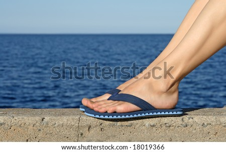 Female feet in blue flip-flops with see in the background. - stock photo