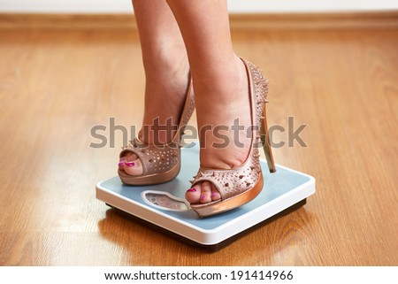 Female feet in golden stilettos with weight scale on wooden floor - stock photo