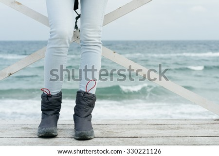 Female feet in jeans and sports boots on wooden boards against the sea close-up. - stock photo