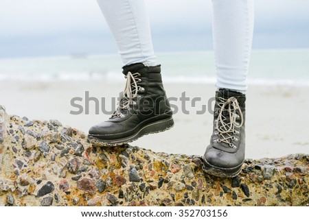 Female feet in jeans and winter boots standing on a stone on the coast close-up - stock photo